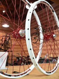 white rims with red spokes and hubs custom built by red barn bicycles