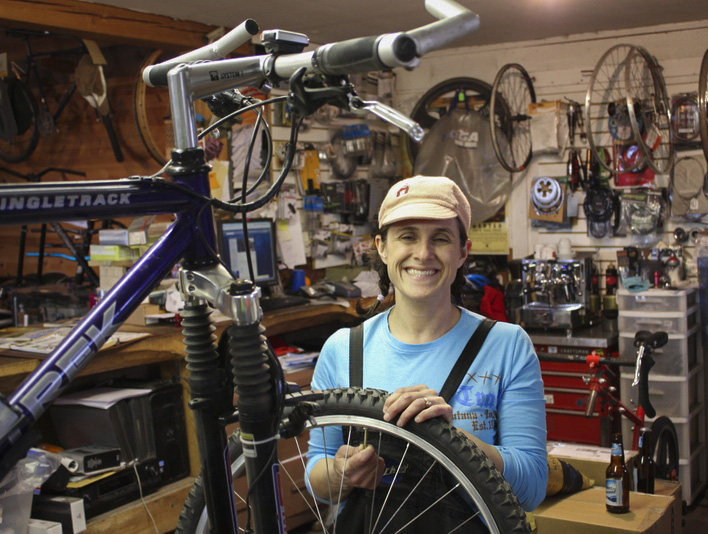 woman mechanic doing service on mountain bike