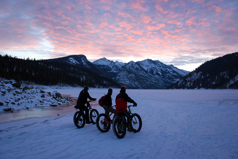 three bikers in winter at como lake montana